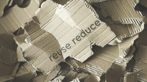 Image of torn cardboard with the words reuse, reduce written on it.