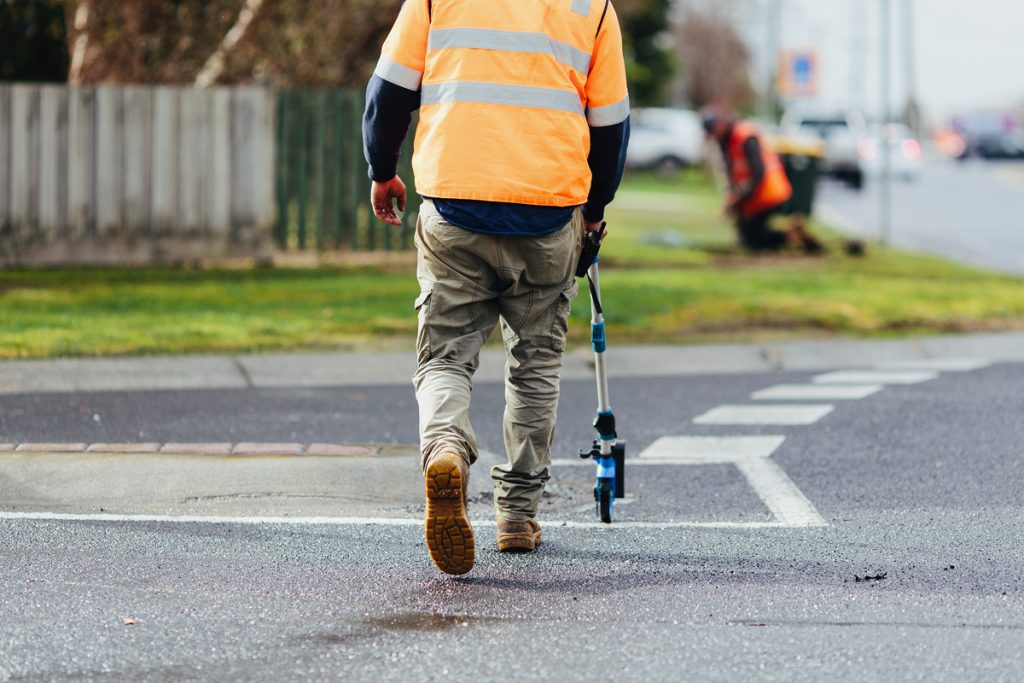A man walking across a road using a measuring wheel