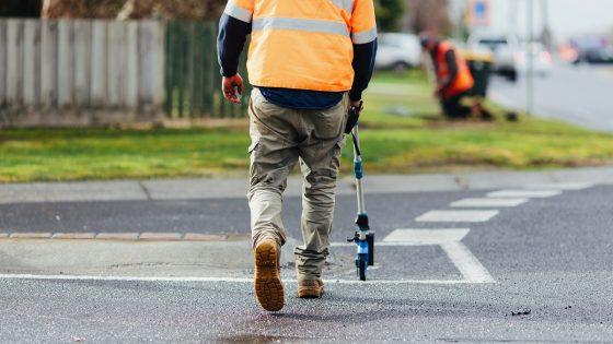 A man walking across a road using a measuring wheel